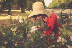 Young woman standing amongst roses in park Stock Photo