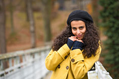 Young woman standing autumn park yellow coat Royalty Free Stock Photo