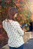 Young woman standing in an autumn street texting on her mobile phone. Typing in a message with her back to the camera and colorful foliage on a creeper covered stock images