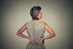 Young woman standing with backache back pain. Isolated on gray background Royalty Free Stock Photography