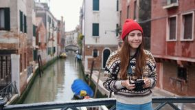 Young woman standing on a background of a water channel and take a photo. Mid shot stock footage