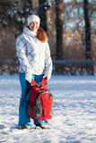 Young woman standing with backpack in winter park Royalty Free Stock Image