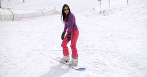 Young woman standing balancing on a snowboard Stock Photography