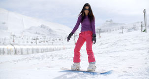 Young woman standing balancing on a snowboard Royalty Free Stock Photo