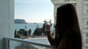 Young woman standing on balcony and drinking water outside. stock footage