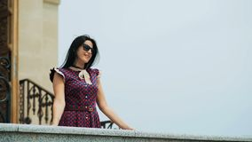 Young woman standing on a balcony, looking forward and smiling stock video