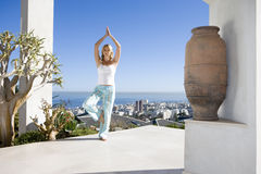 Young woman standing on balcony in tree pose yoga stance, portrait Stock Photo