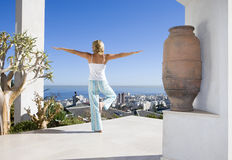 Young woman standing on balcony in tree pose yoga stance, rear view Stock Photo