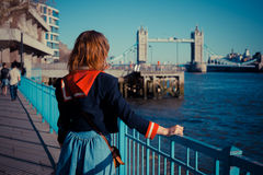 Young woman standing on the bank of the Thames. Young woman is standing on the bank of the river Thames in London on a sunny day royalty free stock photos