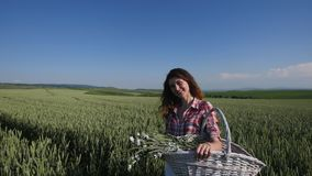 Young woman standing with basket with flowers a wheat field with blue sky on the background stock footage