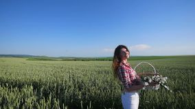 Young woman standing with basket with flowers a wheat field with blue sky on the background. slow motion stock video
