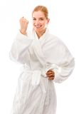 Young woman standing in bathrobe celebrating success Stock Photo