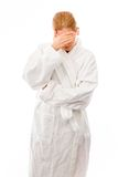 Young woman standing in bathrobe covering her face with her hand Stock Photo