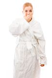 Young woman standing in bathrobe with hand over her mouth Stock Images