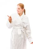 Young woman standing in bathrobe and pointing Stock Photography