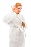 Young woman standing in bathrobe and showing ok sign Stock Photo