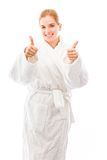 Young woman standing in bathrobe showing thumbs up towards camer Royalty Free Stock Photos