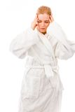 Young woman standing in bathrobe suffering from headache Stock Image