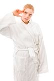 Young woman standing in bathrobe and thinking Stock Image