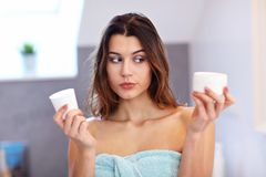 Young woman standing in bathroom and applying face cream in the morning. Picture showing young woman in the bathroom royalty free stock photo