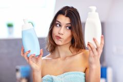 Young woman standing in bathroom and applying face cream in the morning. Picture showing young woman in the bathroom royalty free stock photos