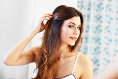 Young woman standing in bathroom in the morning. Picture showing young woman looking in bathroom mirror stock photos