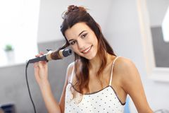 Young woman standing in bathroom in the morning. Picture showing young woman looking in bathroom mirror stock photo