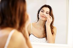 Young woman standing in bathroom in the morning. Picture showing young woman looking in bathroom mirror royalty free stock image