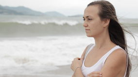 Young woman standing on the beach with bad weather and looking on the sea. stock video footage
