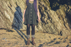Young woman standing on beach with driftwood Stock Image