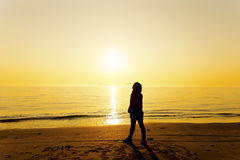 Young woman standing on beach under sunset Stock Photo