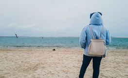 Rear view of girl standing on the beach, wearing a hoodie and staring at the water in solitude. royalty free stock images