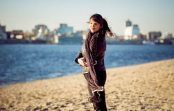 Young woman standing on beach at windy autumn day Royalty Free Stock Images