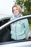 Young woman standing bear a car with opened door Royalty Free Stock Photography