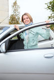 Young woman standing behind a car with opened door Stock Photo