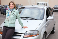Young woman standing behind a new own car Stock Image