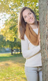 Young woman standing behind tree outdoor in park Royalty Free Stock Photos