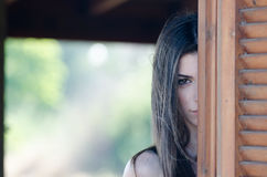 Young woman standing behind of a window Stock Photo