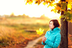 Young woman standing below autumn tree on sunset Stock Images
