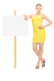 Young woman standing by a blank signboard Royalty Free Stock Photography
