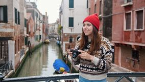 Young woman standing on the bridge on a background of a water channel and take a interesting photo. Mid shot stock video footage