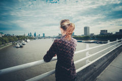 Young woman standing on bridge in city Stock Photos