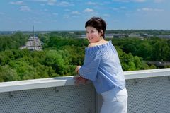 Young woman standing on the bridge with highway in the background and looking at camera stock images