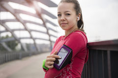 A young woman standing on the bridge pointing at her phone in an armband looking into a camera. Royalty Free Stock Photo