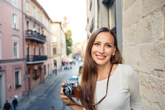 Young woman standing with camera at the balcony Royalty Free Stock Photo