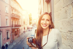 Young woman standing with camera at the balcony Stock Images