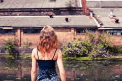 Young woman standing by canal Stock Photo