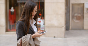 Young woman standing checking her mobile Royalty Free Stock Image