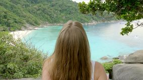 Woman on Top of the Cliff. Young woman standing on cliff`s edge,raising hands up and looking into a wide valley and lagoon. Vacation,adventure and lifestyle stock video