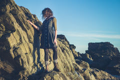 Young woman standing on a cliff Stock Photography